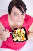 Overweight Woman Eating A Fruit Salad. Selective Focus.