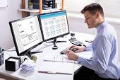 Businessman Calculating Invoice In Office poster
