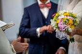 The Bride Holds A Wedding Bouquet Of Beautiful Flowers In Her Hand. The Bouquet Consists Of White, Y poster