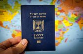 Hand Holding The Passport Of The State Of Israel Against The Colorful World Map Atlas. Israel Citize poster