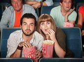stock photo of bleachers  - Scared Caucasian couple eating popcorn in theater - JPG
