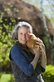 foto of geodesic  - Woman holding chicken outside her geodesic home - JPG