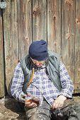 Homeless leaning against barn door