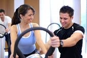 Personal Trainer Explaining A Vibration Plate In A Gym To A Female Customer