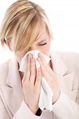 stock photo of respiratory disease  - Young blonde woman is suffering from a cold or flu and is sneezing into a tissue - JPG