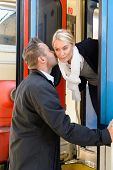 Man kissing woman goodbye on cheek train leaving friends commuter