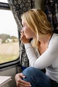 Woman smiling and looking out train window leisure travel vacation