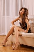 Beautiful Woman Sitting On Sofa