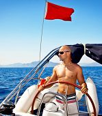 Photo of handsome muscular man at the helm of ship, sailing at Mediterranean sea, traveling the worl