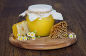glass jar of honey and honeycombs on wooden background