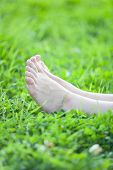 Barefooted Female Legs On Green Grass Background