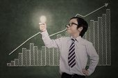 Confident Business Boy Holding Lit Bulb On Bar Chart