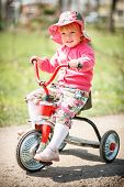 picture of tricycle  - little girl driving a tricycle in park smiling happy - JPG