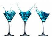 Blue alcohol cocktail set with splash on white