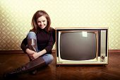art portrait of young smiling ecstatic woman sitting near retro tv set in room with vintage wallpaper, stylization 60-70s, toned