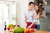Young Beautiful Woman Embracing Man Working In Kitchen