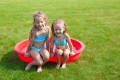 Two Little Sisters In Small Pool Have Fun