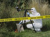 stock photo of safety barrier  - Forensic scientist checking for evidence behind a crime scene barrier - JPG