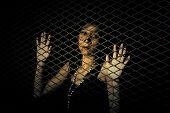 stock photo of slavery  - Woman behind a metal fence - JPG