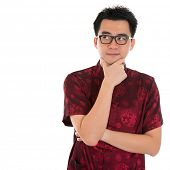 Asian man with Chinese traditional cheongsam or tang suit having a thought.  Male model isolated on