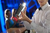 stock photo of bartender  - Bartender shaking a cocktail young women on the background - JPG