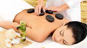 Woman Having Hot Stone Massage Of Back In Spa Salon