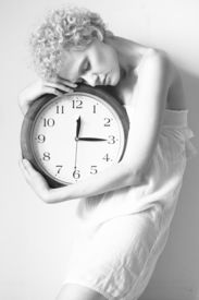 picture of emaciated  - Conceptual portrait of girl in bed with big clock - JPG