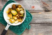 stock photo of saucepan  - Delicious browned sauteed diced brussels sprouts in a saucepan on an oven cloth overhead view on an old rustic weathered wooden table top with grungy boards and copyspace - JPG