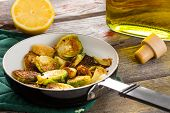 foto of sauteed  - Succulent sauteed brussels sprouts cooked in tangy lemon and olive oil displayed in the saucepan on an old wooden table close up side view - JPG