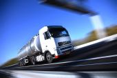 stock photo of fuel tanker  - A white tanker truck on a highway traveling at full speed