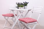 Garden chairs and table with flowers on white background