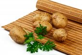 potato tubers with a sprig of parsley on the mat