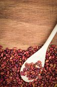 Red beans and a wooden spoon on a wood background with space for text