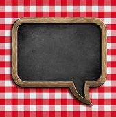 menu chalkboard speech bubble on table with red picnic tablecloth