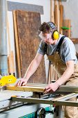 Carpenter working on an electric buzz saw cutting some boards, he is wearing safety glasses and hear