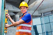 Asian Indonesian builder or craftsman with hardhat and bubble level controlling or checking a wall of a tower building or construction site