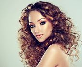 A beautiful girl with long curly hair and fashion make-up