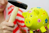 Breaking A Porcelain Piggy Bank With A Hammer