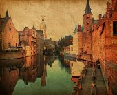 Bruges historic centreat the evening . The classic view from the Rozenhoedkaai. Belgium. Photo in retro style. Added paper texture.