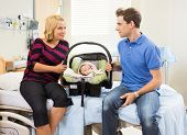Mid adult couple with baby carrier looking at each other while sitting on hospital bed