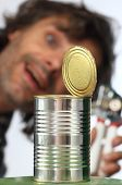 stock photo of tin man  - happy blurred man with an open tin can - JPG