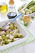 stock photo of brussels sprouts  - Roasted brussels sprouts with red onions and pears in a baking dish white, decoration: balsamic vinegar , olive oil, raw brussels sprouts and pears.