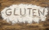 gluten word written  in wheat flour on wooden board