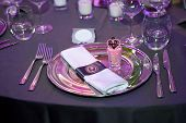Detail of a wedding dinner setting with purple reflection on the tableware