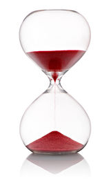 stock photo of pass-time  - Hourglass with red sand running through the clear glass bulbs measuring the passing time in a countdown to the finish standing at the half way position on a white background - JPG
