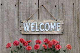 pic of wooden fence  - Wood welcome sign hanging on wooden fence with mum border - JPG