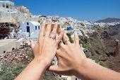 Honeymoon On Santorini Island - Hands With Wedding Rings Over Panorama Of Oia Village