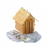 House built out of puzzle pieces with money and golden abacus