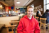 Smiling college student sitting in a coffee shop