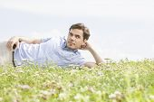 Thoughtful young man lying on grass against sky